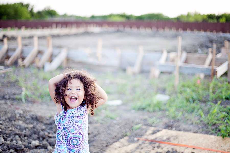 little girl standing in front of a new home foundation
