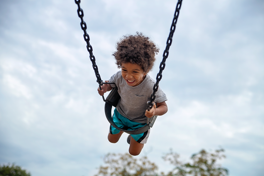 Swinging son active biracial boy