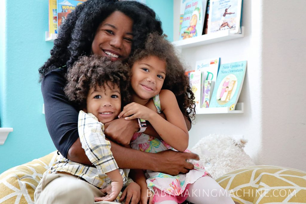 We're on spring break!: Black mom hugging her biracial kids.