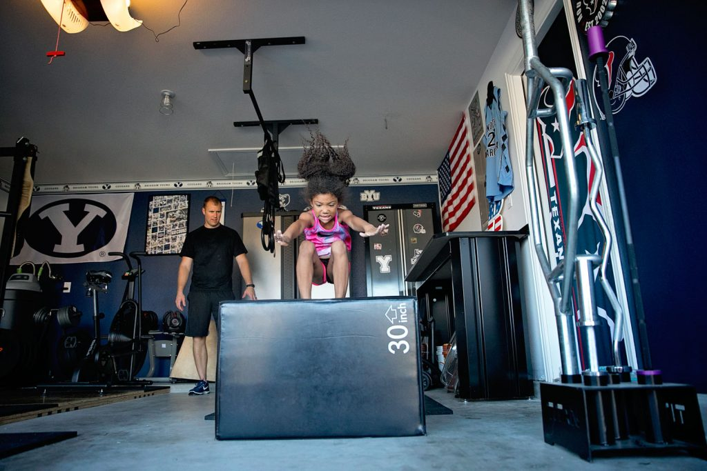 little girl doing box jumps in a garage man cave