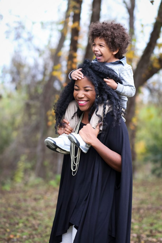 Black mom with her biracial son being held on her shoulders.