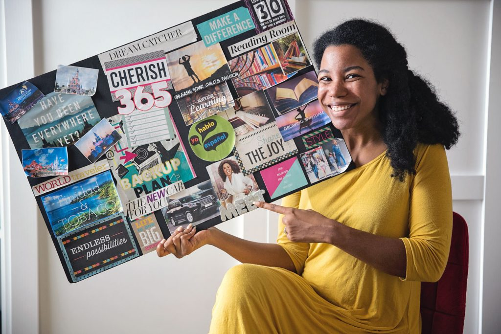 vision board example: An African American woman holding her vision board and sharing how to make a vision board that works.