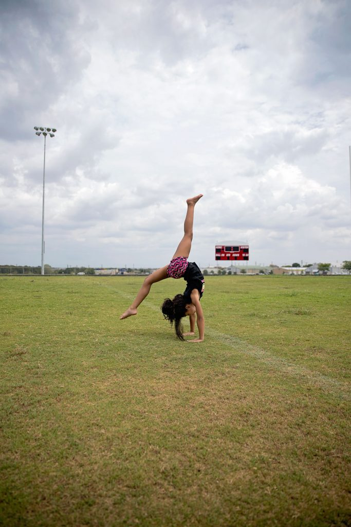 biracial competitive cheerleader doing a back walkover