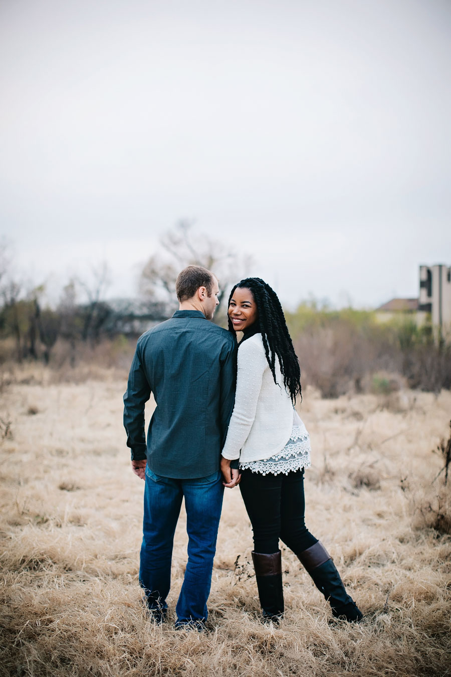 Interracial married couple standing in a field holding hands.