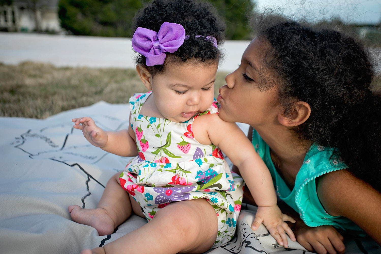 A big sister and baby sister sharing a kiss