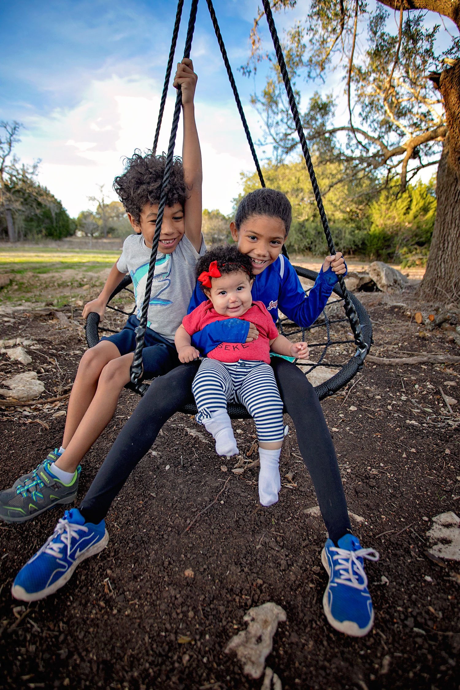 Baby that's 9 months old swinging with her two older siblings