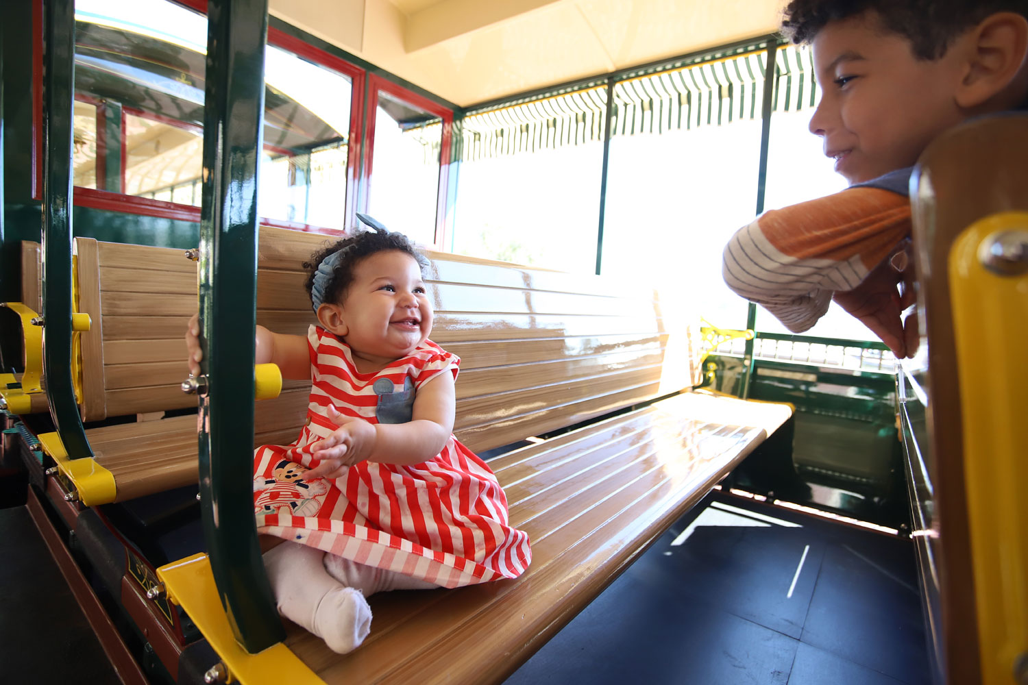 A baby girl playing with her big brother on a train.
