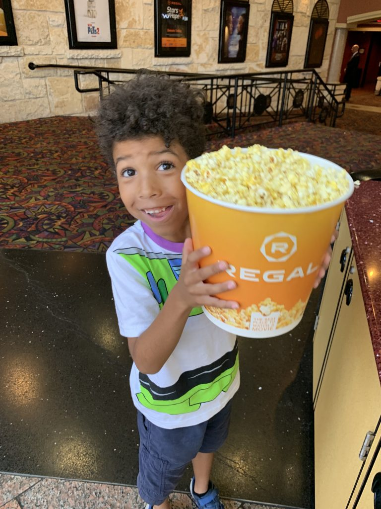 biracial boy dressed up like Buzz Lightyear with a giant tub of popcorn before watching toy story 4