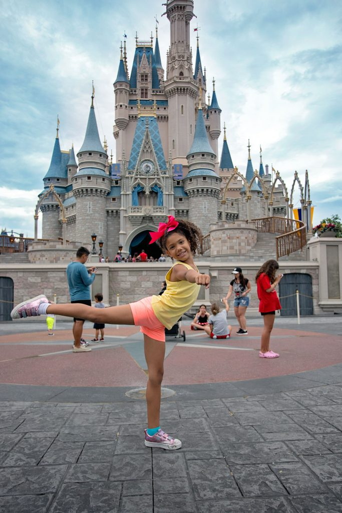 Cheerleader posing in front of the Disney World castle