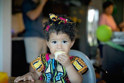 Biracial baby girl eating a birthday cupcake