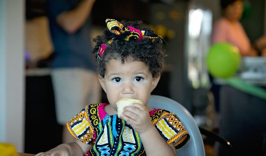 Biracial baby girl eating a birthday cupcake