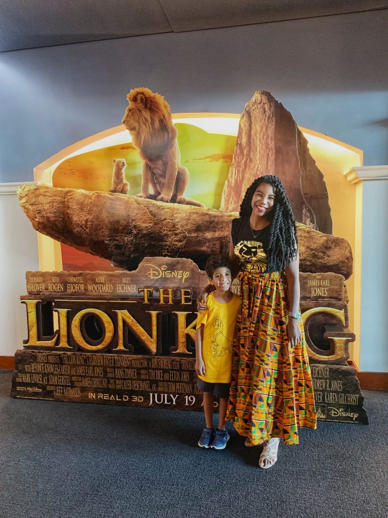 Live action lion king kids review. Mother son photo in front of the Lion King poster.