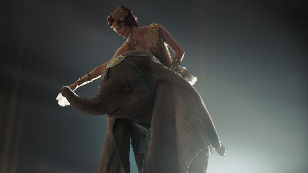 A woman sit atop Dumbo in the new live action movie. Dumbo review.