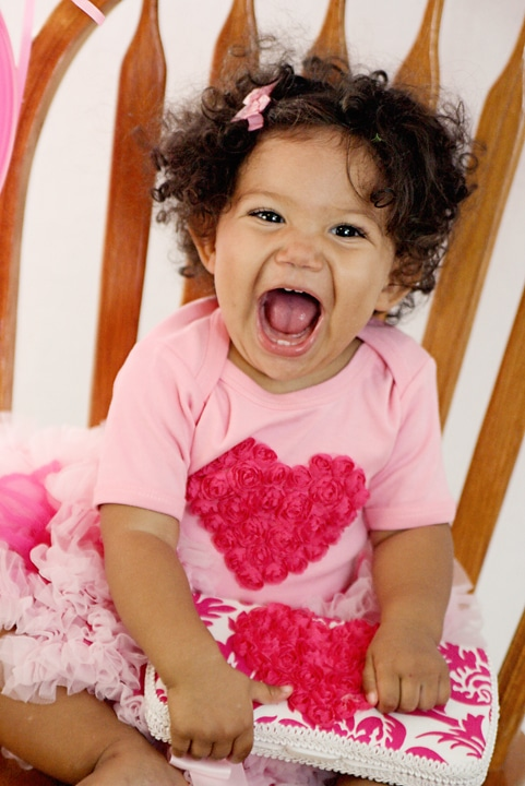 biracial toddler girl with a big smile wearing a hear valentines shirt