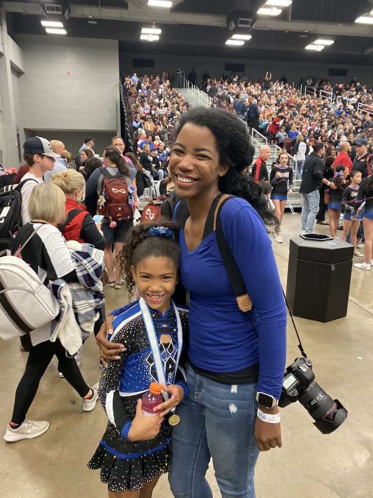 Mother and biracial cheerleader daughter embracing at a cheer competition.