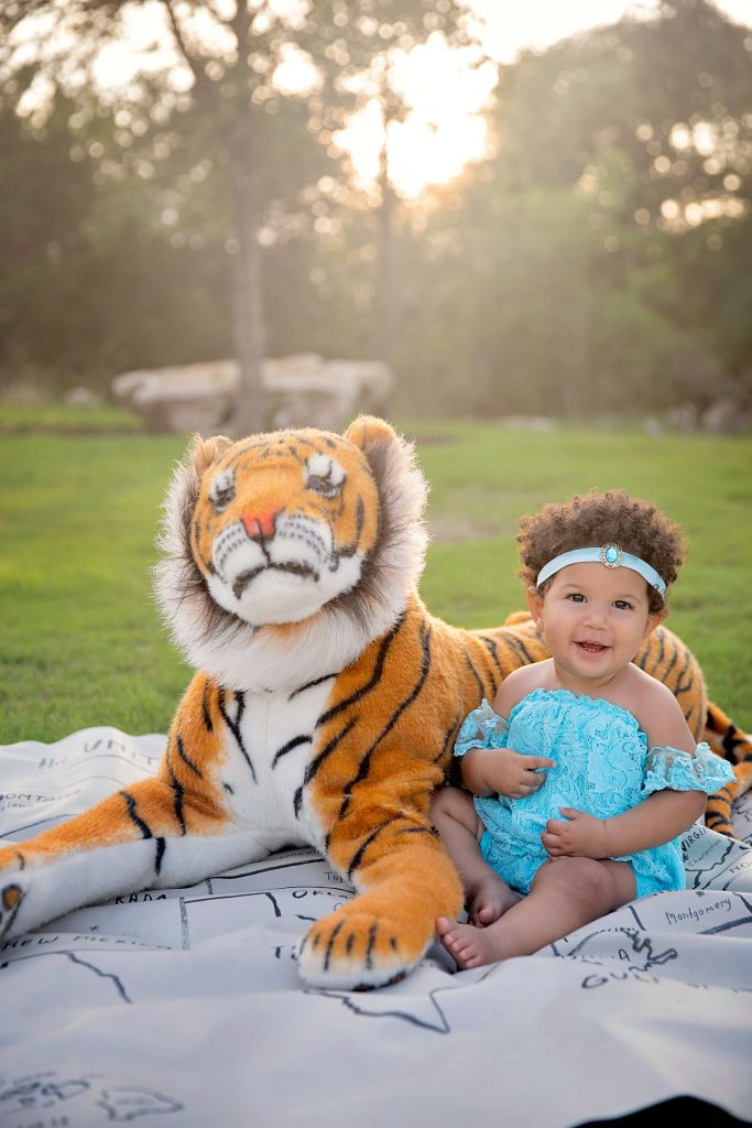 Biracial toddler girl dressed as princess Jasmine with a giant stuffed tiger as Raja