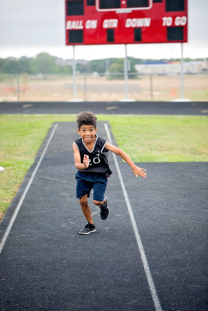 biracial boy running on a track field