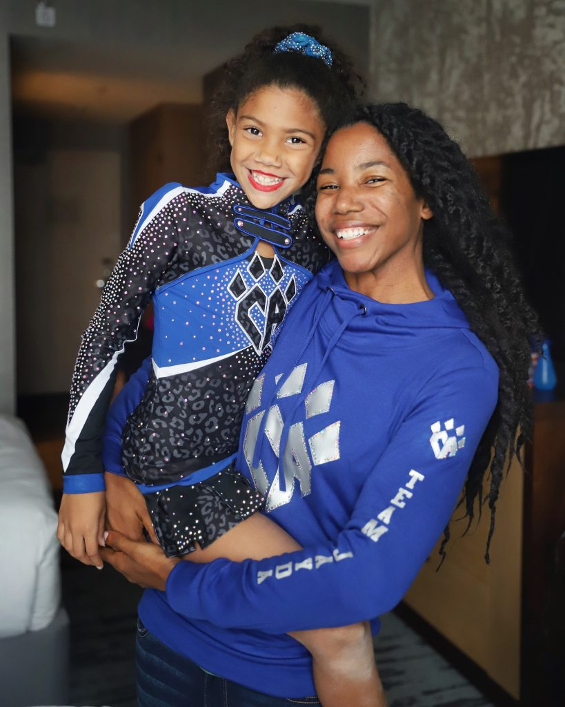 Cheer mom holding her cheerleader daughter wearing a cheer athletics uniform explaining cheer mom life