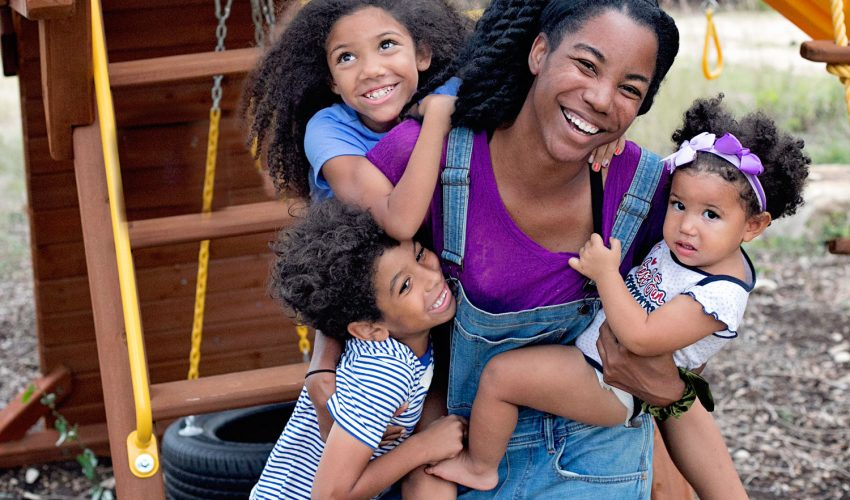 Black mom holding her three biracial children