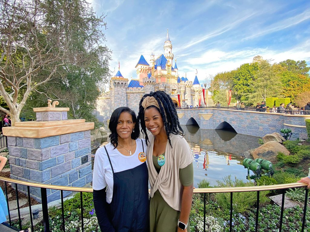 Mother daughter generational trip to Disneyland. A photo taken of two black women in front of the Disneyland castle before going to Batuu to ride Rise of the Resistance