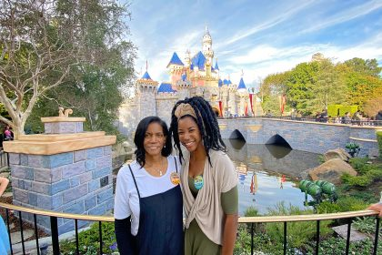 two black women posing for a photo in front of the disneyland castle