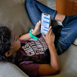 Biracial girl holding a cell phone on Internet safety day.