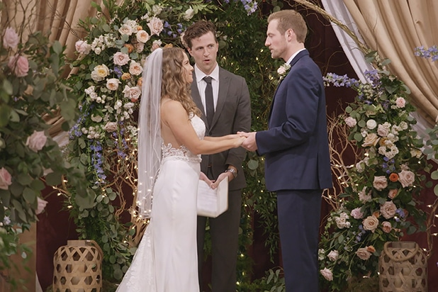 Kenny and Kelly from netflix love is blind are bride and groom stand hand in hand at the wedding alter