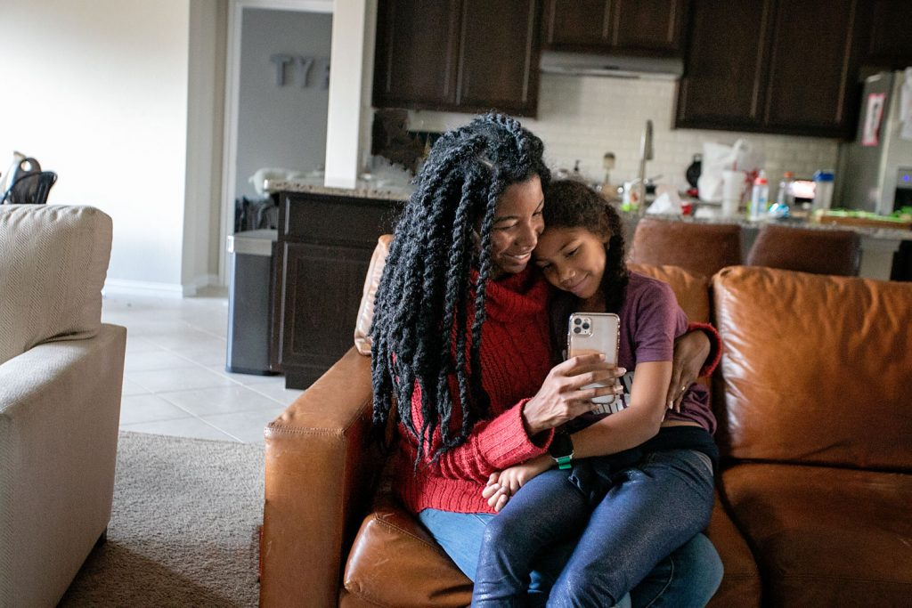 A black bother with her biracial daughter sitting together to have a tech talk about cell phones.