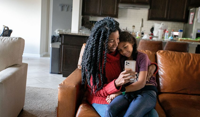 A black bother with her biracial daughter sitting together to have a tech talk about cell phones for internet safety day.