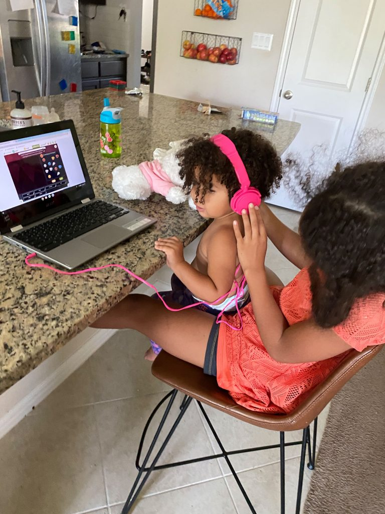 Biracial toddler and her big sister sitting near a laptop wearing pink kids headphones