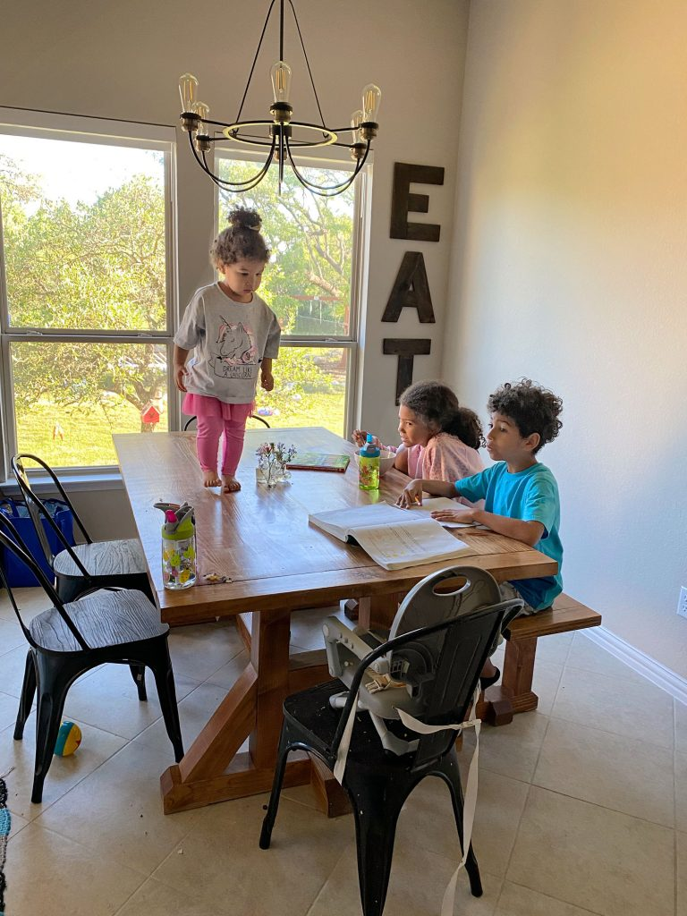 Interracial toddler standing on the kitchen table wit hher siblings homeschooling beside her