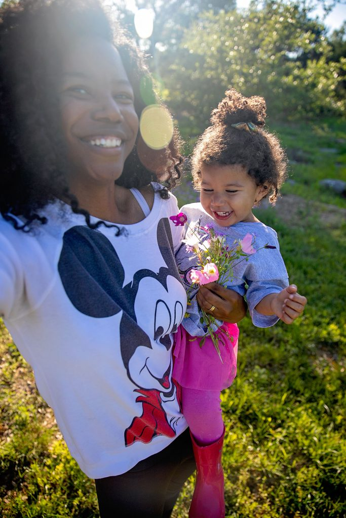 Black mom and biracial toddler holding wildflowers outside