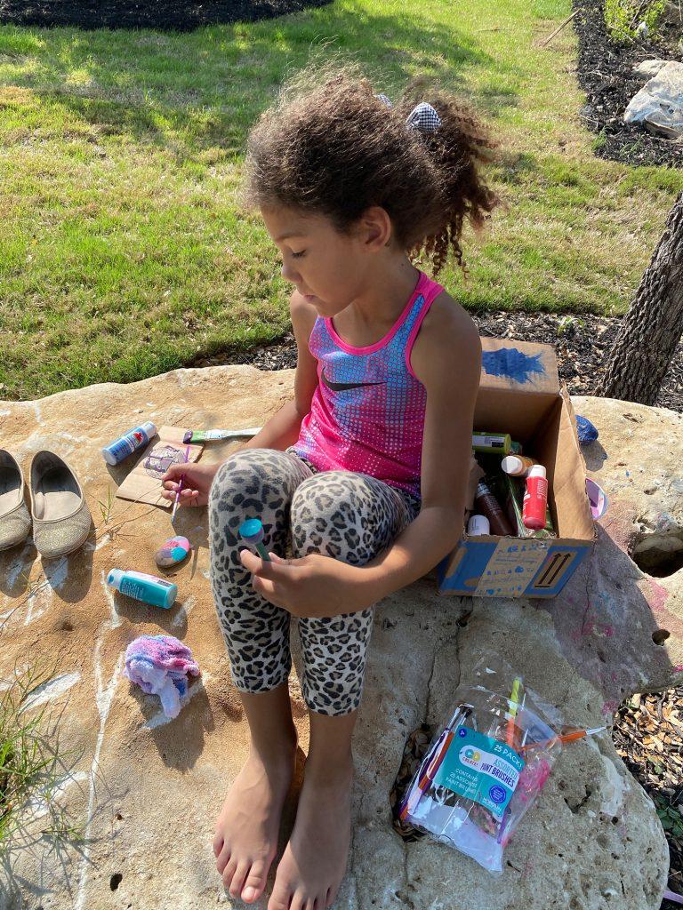 Biracial girl painting rocks as a natural craft project.