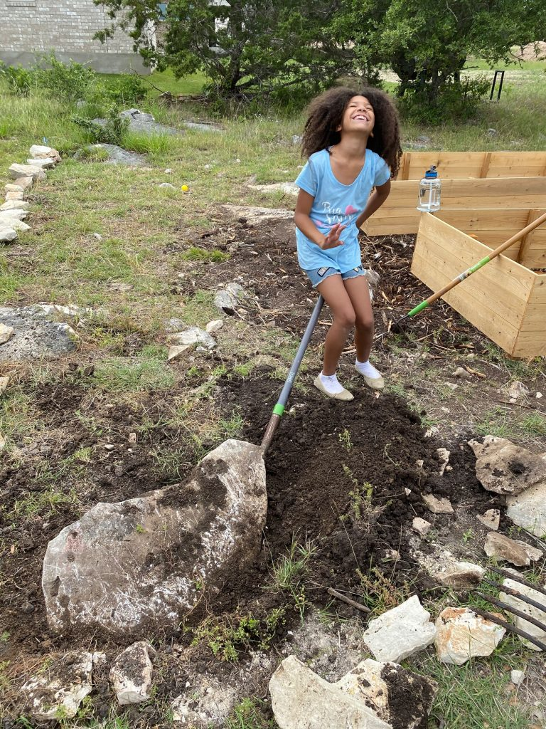 Biracial girl with big curly hair pulling a rock out of the ground wit ha shovel