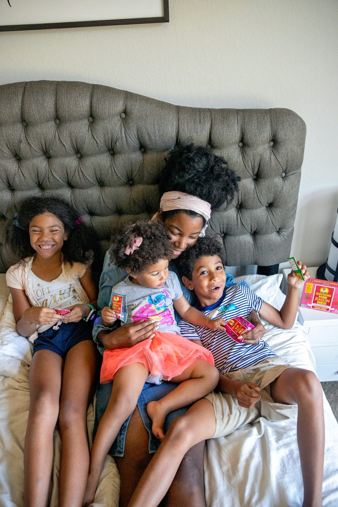 Black mother cuddling with her three biracial children eating raisins. Examples of quality time with kids.