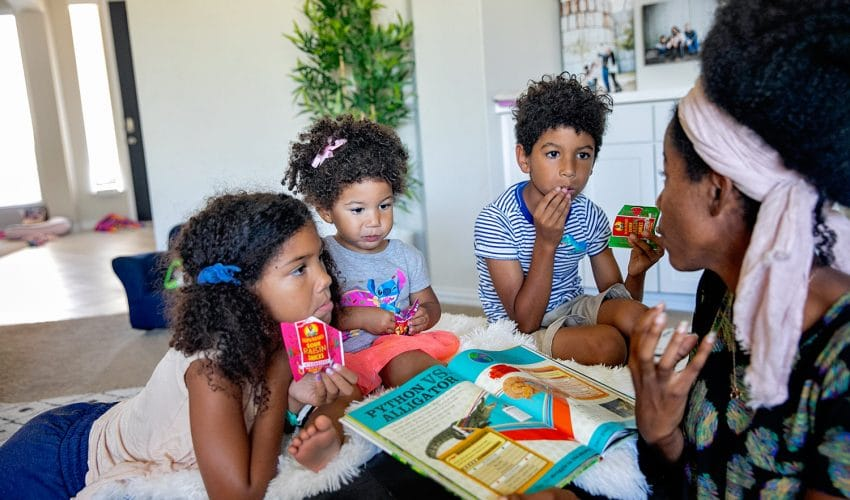 Black mother reading to her biracial children sharing tips on quality time with kids