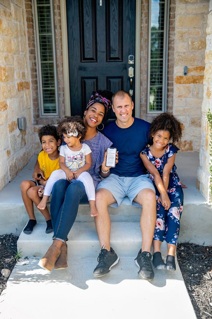 Interracial family smiling about their paid off mortgage on their front porch