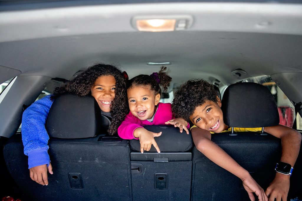Biracial kids in back of car getting ready for a holiday road trip.