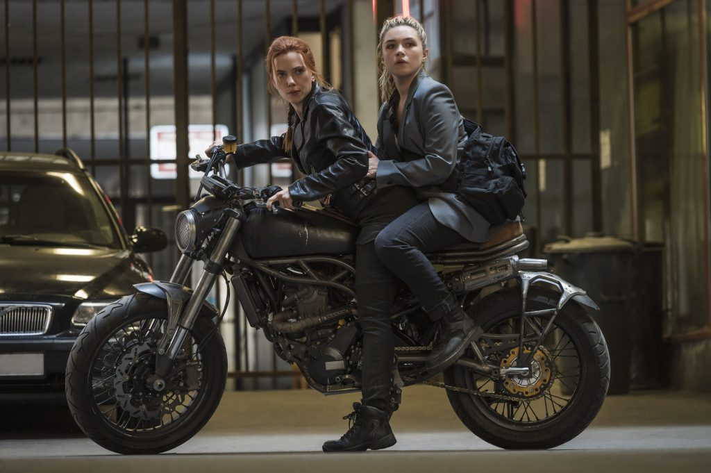 Two female characters in Marvel's Black Widow riding on a motorcycle.