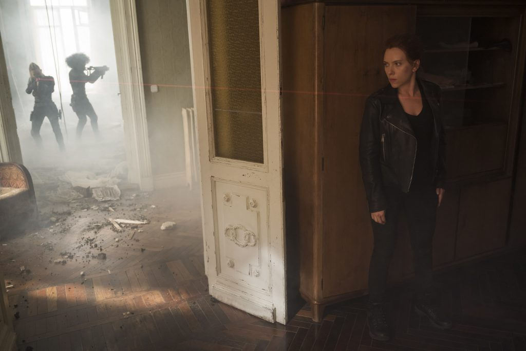 Black widow hides behind a wall in an action scene for the movie