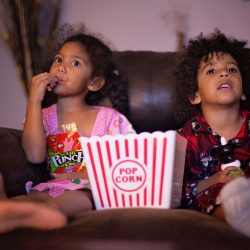 family movie night kids eating popcorn and watching a show