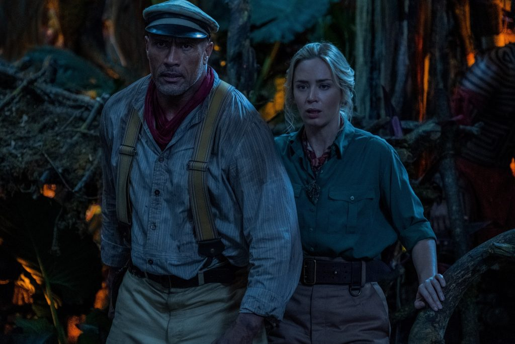 Emily Blunt and Dwayne Johnson walk in a dark and scary cave in Disney's Jungle Cruise