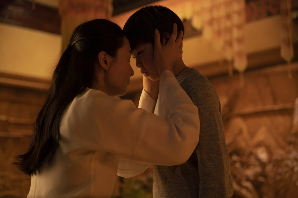 Shag-chi family movie Marvel film. Mother and son kneel together in an endearing embrace