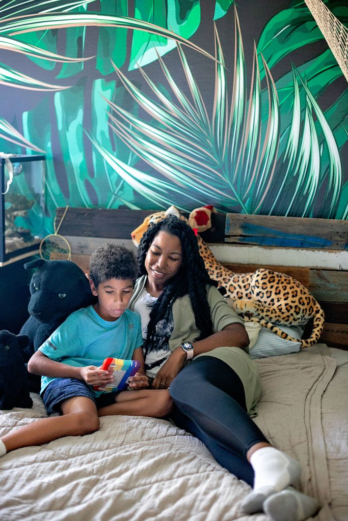 black mother reading a kid-friendly tablet on a bed with her son