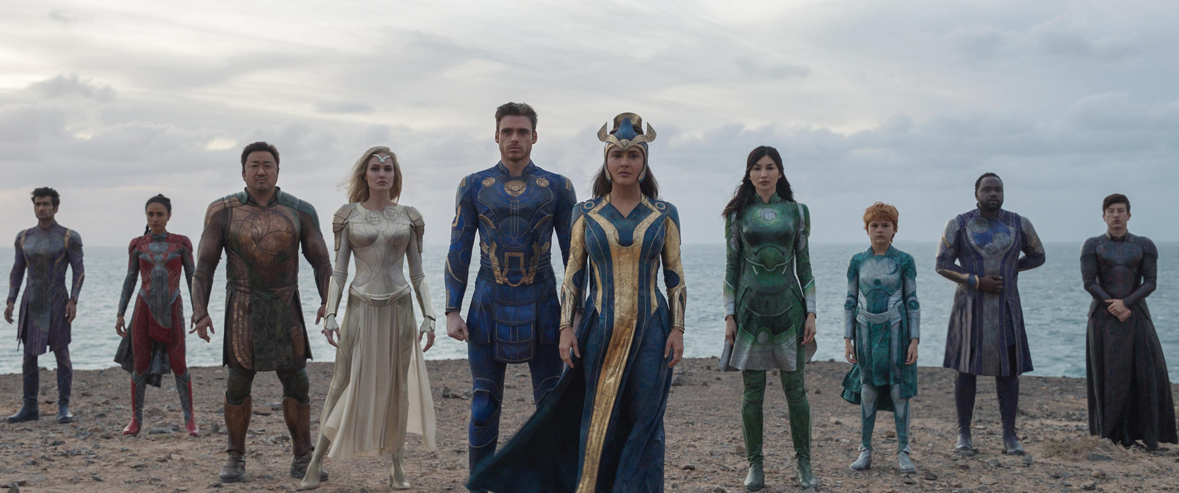 Ten Marvel Eternals characters standing side by side on a beach